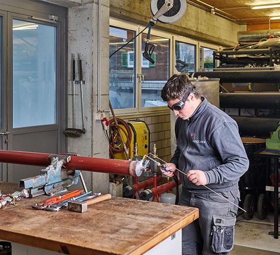 Junger Berufsmann in der Werkstatt bei Schweissarbeiten an einem Rohr